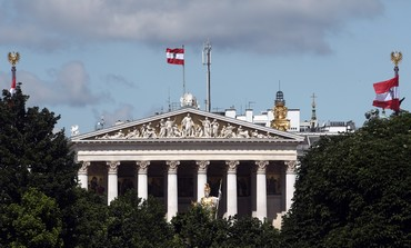 Austrian national flags are seen above the parliament house in Vienna