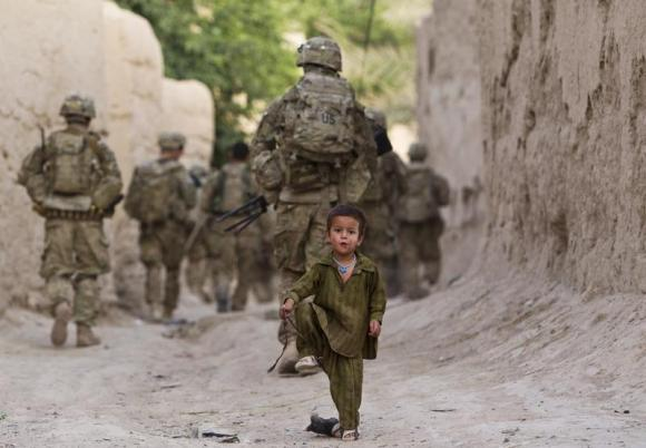 A boy plays on a street as U.S. Army soldiers of the Battle company, 1-508 Parachute Infantry battalion, 4th Brigade Combat Team, 82nd Airborne Division, patrol during a mission in Zahri district of Kandahar province, southern Afghanistan May 30, 2012.