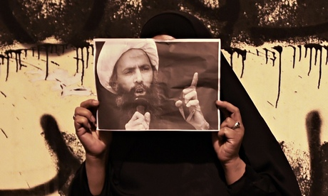 A woman near Manama, Bahrain, holds up a portrait of Shia leader Nimr Baqir al-Nimr in solidarity. Photograph: Mohammed Al-Shaikh/AFP/Getty Images
