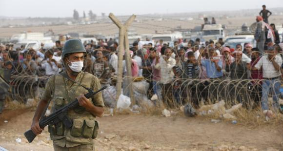 A Turkish soldier stands guard as Syrian Kurdish refugees wait behind the border fences to cross into Turkey near the southeastern town of Suruc in Sanliurfa province September 27, 2014. CREDIT: REUTERS/MURAD SEZER