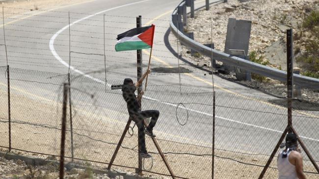 A protester places a Palestinian flag at the Israeli barrier fence in the West Bank village of Rafat near Ramallah. (File photo)