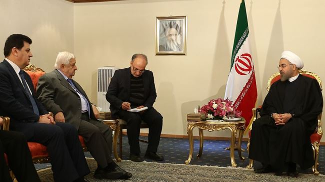 Iran's President Hassan Rouhani (R) receives Syrian Foreign Minister Walid Muallem (2nd L) in Tehran on December 9, 2014.
