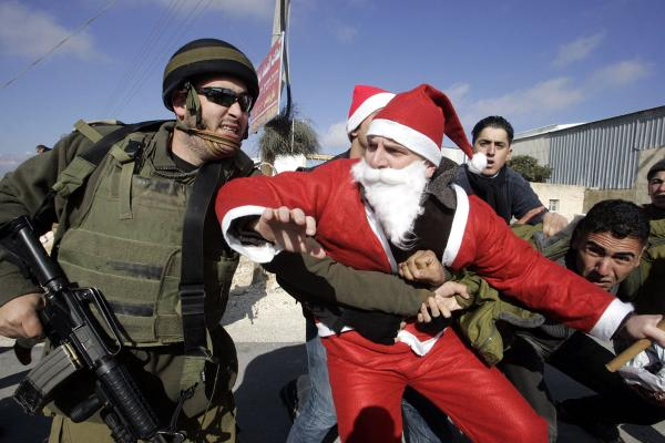 Detaining  >> Israeli Forces Violently Disperse Peaceful Christmas March In