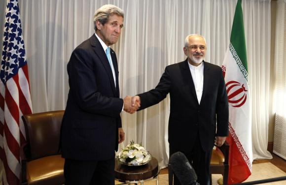 U.S. Secretary of State John Kerry shakes hands with Iranian Foreign Minister Mohammad Javad Zarif before a meeting in Geneva January 14, 2015. Credit: Reuters/Rick Wilking