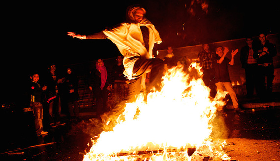An Iranian woman jumps over a bonfire in southern Tehran on March 19, 2013, during the Wednesday Fire feast, or Chaharshanbe Suri. (photo by BEHROUZ MEHRI/AFP/Getty Images)