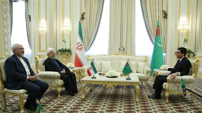Iranian President Hassan Rouhani (2nd L) talks with his Turkmen counterpart Gurbanguly Berdimuhamedow in Ashgabat on March 11, 2015.