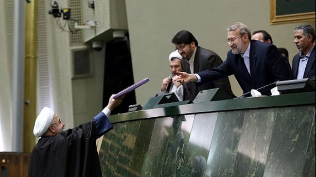 Iranian President Hassan Rouhani (L) submits the draft budget for the next Iranian fiscal year to Majlis Speaker Ali Larijani on December 7, 2014.