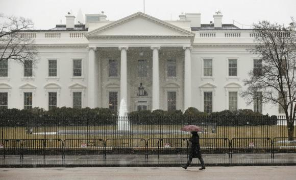 Snow starts to fall as a woman walks past the White House in Washington March 5, 2015. CREDIT: REUTERS/KEVIN LAMARQUE
