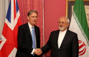 Iran FM Zarif shakes hands with UK Foreign Secretary Hammond on Mar. 29, 2015.