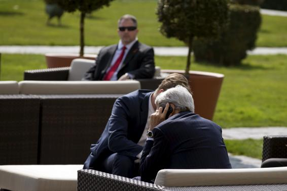 U.S. Secretary of State John Kerry (front) talks on the phone while waiting for lunch following a morning meeting with Iran's Foreign Minister Mohammad Javad Zarif over Iran's nuclear programme in Lausanne March 19, 2015. REUTERS/Brian Snyder