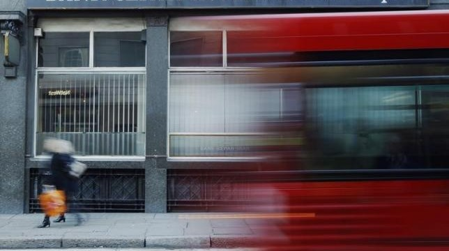 A red London bus passes a branch of Iranian owned Bank Sepah International in London